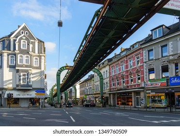 Wuppertal, Germany - March 2019: Outdoor view of Schwebebahn, famous historical landmark Suspension Monorail, carriage hanged from steel rail structure over street through Wuppertal city, Germany.