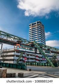 "Wuppertal, Nordrhein-Westfalen, Germany. 15.01.2012. Monorail ""Die Schwebebahn"", built 1901, passing by the highrise of Stadtsparkasse Wuppertal in Wuppertal-Elberfeld, Germany."