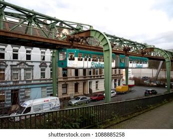 """Wuppertal, Nordrhein-Westfalen, Germany. 15.01.2012. Monorail """"Die Schwebebahn"""", built 1901,  running overhead the Sonnborner Strasse in Wuppertal-Sonnborn."""