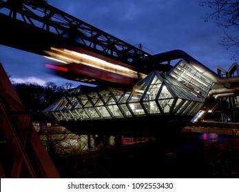 "Wuppertal, Nordrhein-Westfalen, Germany. 15.01.2012. Monorail ""Die Schwebebahn"", built 1901,  pulling into the station Oligser Muehle by night in Wuppertal-Elberfeld, Germany."