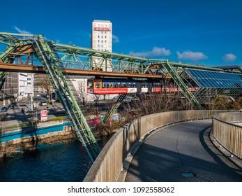 """Wuppertal, Nordrhein-Westfalen, Germany. 15.01.2012. Monorail """"Die Schwebebahn"""", built 1901,  running overhead the Wupper in Wuppertal-Elberfeld, Germany."""