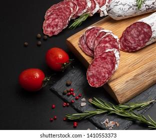 Wurst, Fuet, Sausage sliced on black background.