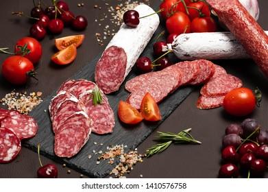 Wurst, Fuet, Sausage sliced on black background. Delicatessen.