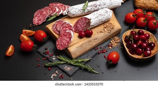 Wurst sliced. Fuet, Sausage sliced on black background.