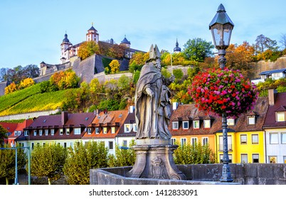 Wurzburg, Bavaria, Germany, view of the Marienberg Fortress from the Old Main Bridge with stone sculpture of religious saint St Burkard