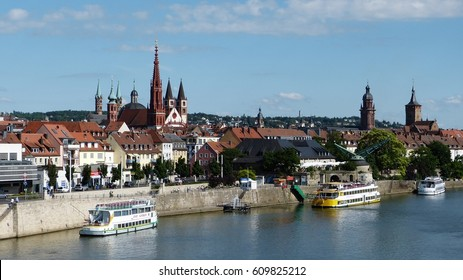 WURZBURG, GERMANY - JUNE 17, 2012. View of river waterfront in Wurzburg, with historical buildings, cruising boats and people.