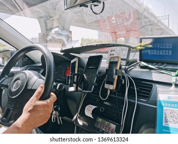 Wuxi, China - April 15, 2019: A typical taxi inside layout, several mobilephones installed different online hailing app. 2D code is for passages to pay with mobile. Chinese on screen is guideline.