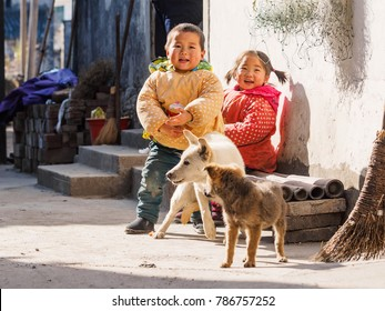 Wuyuan, China - Dec. 21, 2017: Rural Chinese boy play with his dogs in sunny day, funny childhood lifestyle.