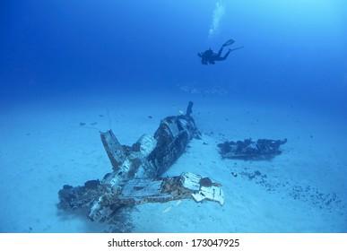 WW2 era Corsair airplane wreck and diver background.