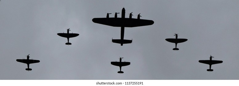 WW2 Lancaster bomber, Hurricane and Spitfire Fighters including clipped wing variant in close formation. In silhouette against a cloudy sky. Black and White