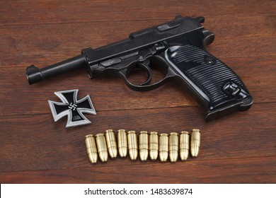WWII era nazi german army handgun with ammunitions and military awards - Iron Cross on wooden table