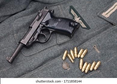 WWII era nazi german army 9 mm semi-automatic pistol with ammunition on army grey uniform background