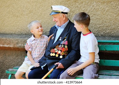 WWII veteran with children. Grandchildren looking at grandfather's military awards.