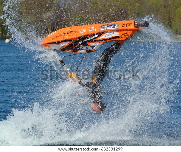 WYBOSTON, BEDFORDSHIRE, ENGLAND -  APRIL 09, 2017: Freestyle Jet Skier  competitor upside down  performing back flip creating at lot of spray.