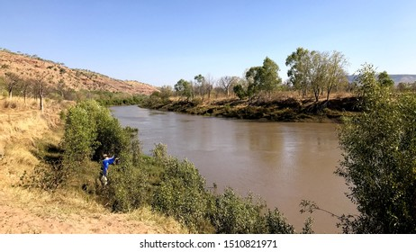 Wyndham, Western Australia - 09 18 2019: Young man throwing his rod into the King River to catch a Barramundi