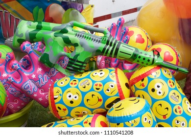 Wyndmoor, PA, USA - June 8, 2018: Inflatable machine guns are among the winning prizes at a carnival's midway games. The toy guns look like AR-15s, the same weapon used in recent school shootings.