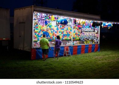 Wyndmoor, PA, USA - June 8, 2018: A couple is talked into taking a chance  at a midway game booth at the annual Wyndmoor Carnival in Wyndmoor, PA.