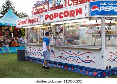 Wyndmoor, PA, USA - June 8, 2018: A man waits for caramel corn at a concession stand at the annual Wyndmoor Carnival in Wyndmoor, PA.