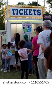 Wyndmoor, PA, USA - June 8, 2018: Attendees wait in line at a ticket booth while two girls check if they meet the height requirements for rides at the annual WYndmoor Carnival in Wyndmoor, PA.