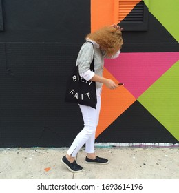 """Wynwood, Miami, FL, USA - November 4, 2013: Woman walking down the streets of Wynwood wearing Madewell clothing and a Madewell purse that reads """"Bein Fait""""."""