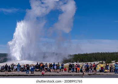 Wyoming, USA - August 10, 2021: Crowds of tourists wait along the boardwalks for Old Faithful to erupt in Yellowstone National Park