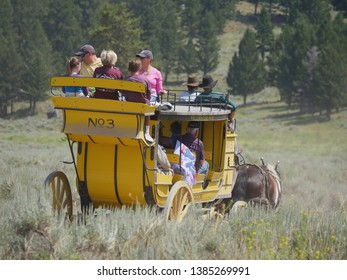 Wyoming, USA--July 2018: Back view of a yellow stagecoach with passengers at Cooke Pass. The stagecoach ride is one of the popular attractions at Yellowstone National Park.