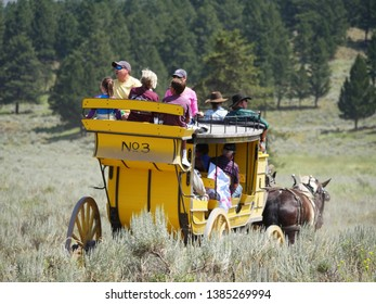 Wyoming, USA--July 2018: Close up of a yellow stagecoach with passengers at Cooke Pass. The stagecoach ride is one of the popular attractions at Yellowstone National Park.