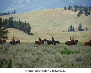 Wyoming, USA--July 2018: Medium close up of horseback riders. Horseback riding is one of the popular activities for tourists at Yellowstone National Park.