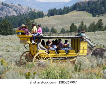 Wyoming, USA--July 2018: Yellow stagecoach with people riding in it. The stagecoach ride is one of the popular attractions at Yellowstone National Park.