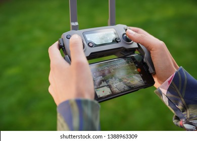 Wysoka, Poland - May 2, 2019: Drone operator holding remote controller of DJI Mavic Pro 2 with Iphone 6s display
