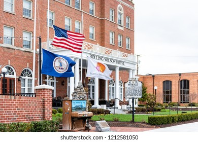 Wytheville, USA - April 19, 2018: Small town village signs flags for historic famous Bolling Wilson boutique hotel in southern south Virginia, historic brick buildings