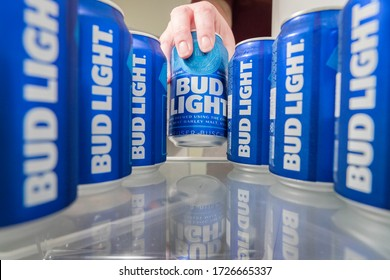 Wytheville, VA USA May 9, 2020 A woman reaches in to a refrigerator to get an ice cold can of Bud Light. Bud Light is an American beer brewed by Anheuser Busch in the US and sold worldwide.