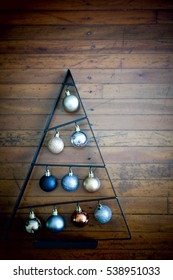 X' mas tree. Metal frame with bubbles, silver rose gold and gold on wooden background.