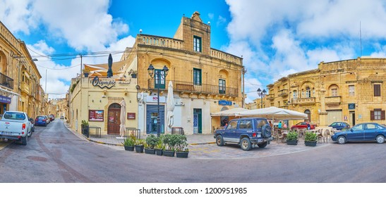 XAGHRA, MALTA - JUNE 15, 2018: Panorama of the old edifices in the central square with outdoor cafes and small stores, on June 15 in Xaghra.