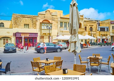 XAGHRA, MALTA - JUNE 15, 2018: The  tables of outdoor cafe in central square with a view on old edifices with stores and restaurants, on June 15 in Xaghra.