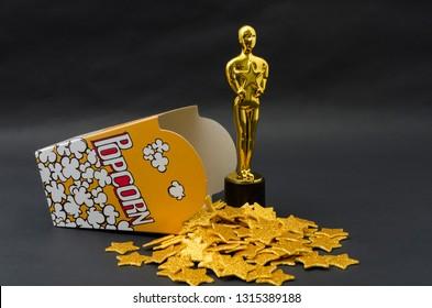Xalapa, Veracruz, Mexico- February 14, 2019: Yellow popcorn box with golden stars and plastic oscar awards against black background