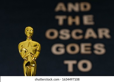 """XALAPA, VERACRUZ, MEXICO- JANUARY 31, 2020: Oscar figurine on a blurred black background with the phrase """"And the Oscar goes to"""" made from wooden letters"""