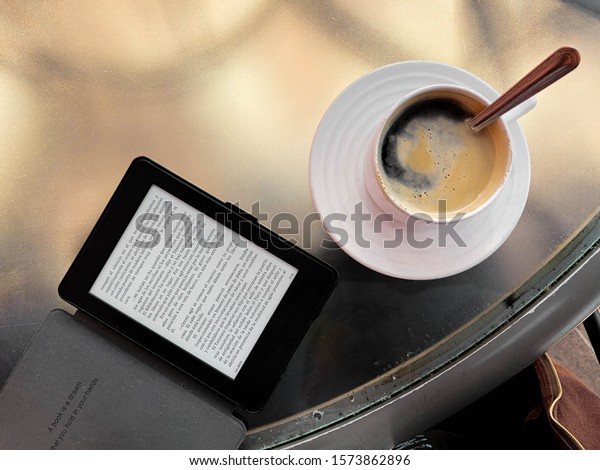 Xalapa, Veracruz / Mexico - November 24 2019: Glass table with cup of coffee with spoon in and Kindle e-reader