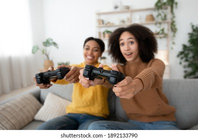 Xbox, enjoying of playing in video game on playstation and rest at home. Smiling surprised excited millennial african american sisters have fun with joysticks in living room interior, free space