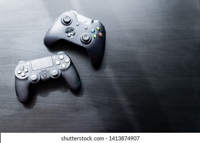 Xbox and Playstation controller sat next to each other on a dark background