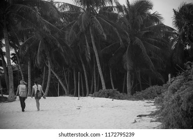 Xcacel, Quintana Roo, Mexico, May 21, 2017 . Two girls walking along a path to the beach with palms