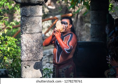Xcaret, Mexico - July 19, 2011: Unkown mayan man playing music on the sea shelf. It's traditional Mayan performance in the jungle of Xcaret park.