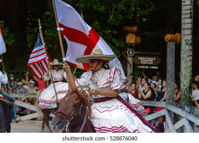XCARET, MEXICO - NOV 7, 2016: Unidentified Mexican cowgirls with different national flags ride horse in the Xcaret park, Mexioc