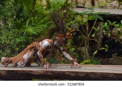 XCARET, MEXICO - NOV 8, 2015: Unidentified man wears a costume of a Maya indian and walks trough the jungle. The Mayan are a group of Indigenous people of Mesoamerica