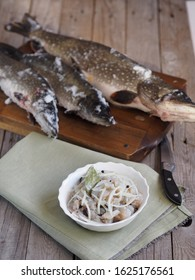 XE salad of freshly salted pike river fish on the background of pike river fish on a cutting board in the kitchen. We chop the pike on the fillet and prepare the XE salad.