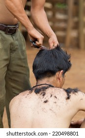 XEKONG, LAOS, APRIL 13 : An unidentified man haircut with clipper at ground in the village of Xekong, Laos, on April 13, 2014