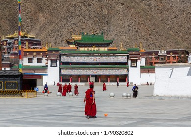 Xiahe, Gansu Province / China - April 28, 2017: View at a square at Labrang Monastery. With red robed monks. Temple buildings with golden and green roofs in the background.