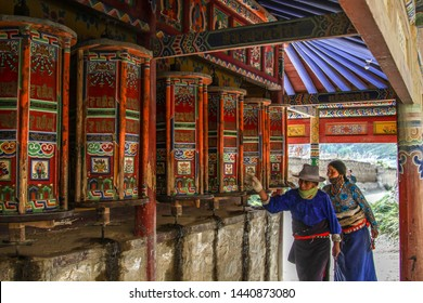 Xiahe, Gansu Province, China - October 2018: buddhist pilgrims walking along the Kora (Corridor of Prayer Wheels) in Labrang Monastery