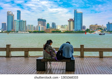 XIAMEN, CHINA -OCTOBER 12: People sitting at the waterfront area of Gulangyu with Xiamen city skyline in the distance on October 12, 2018 in Xiamen
