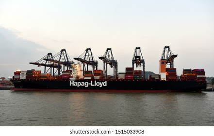 Xiamen, Fujian / China - 15 September 2019: Large container ship owned by Hapag-Lloyd berthing in the container terminal. Gantry cranes are discharging cargo in the containers.